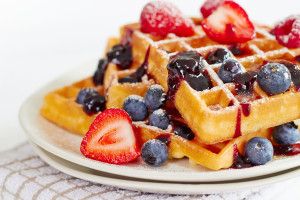Waffles with berries and honey on wooden table ** Note: Visible grain at 100%, best at smaller sizes